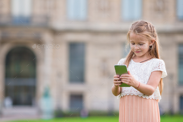 Adorable toddler girl with phone in Paris during summer vacation - Stock Photo - Images