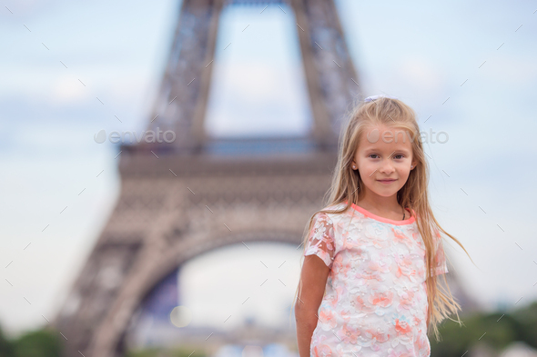 Adorable little girl in Paris background the Eiffel tower during summer vacation - Stock Photo - Images