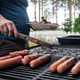 Young caucasian man hands preparing sausages on grill outdoor - PhotoDune Item for Sale