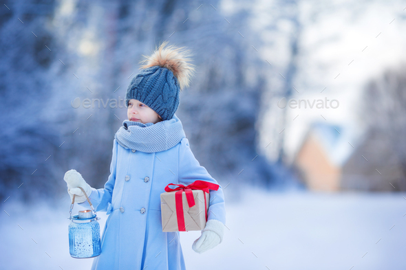 Adorable girl with christmas box gift in winter outdoors on Xmas eve - Stock Photo - Images
