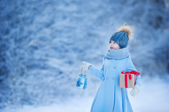 Adorable girl with lamp and christmas box gift in winter on Xmas eve outdoors - Stock Photo - Images