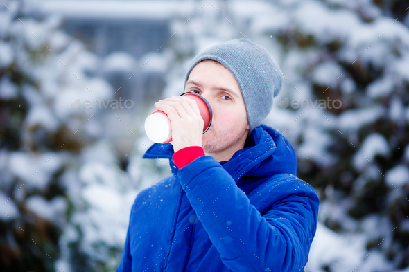Young caucasian man drinking coffee in frozen winter day outdoors - Stock Photo - Images