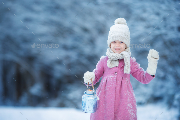 Adorable little girl with flashlight in cold day on Christmas outdoors - Stock Photo - Images