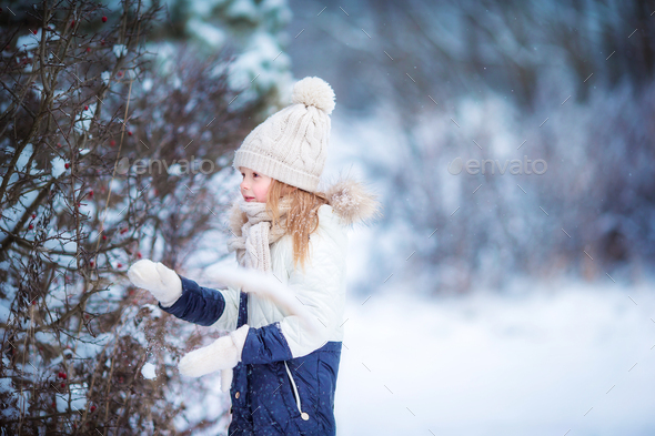 Adorable little girl in frozen winter day outdoors - Stock Photo - Images
