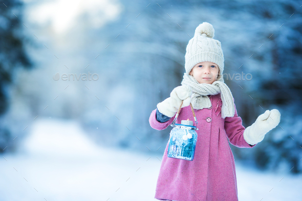 Adorable girl with lamp and candle in winter on Xmas eve outdoors - Stock Photo - Images