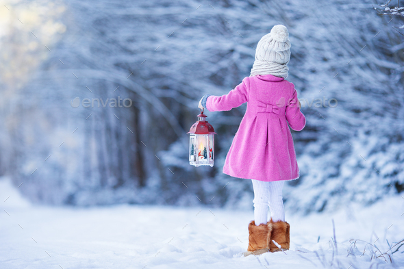 Back view of adorable girl with flashlight on Christmas outdoors - Stock Photo - Images