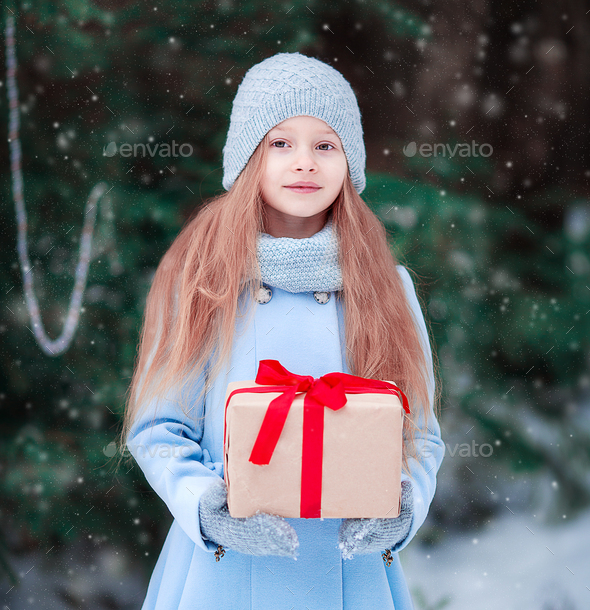 Adorable little girl with christmas box gift in winter outdoors on Xmas eve - Stock Photo - Images