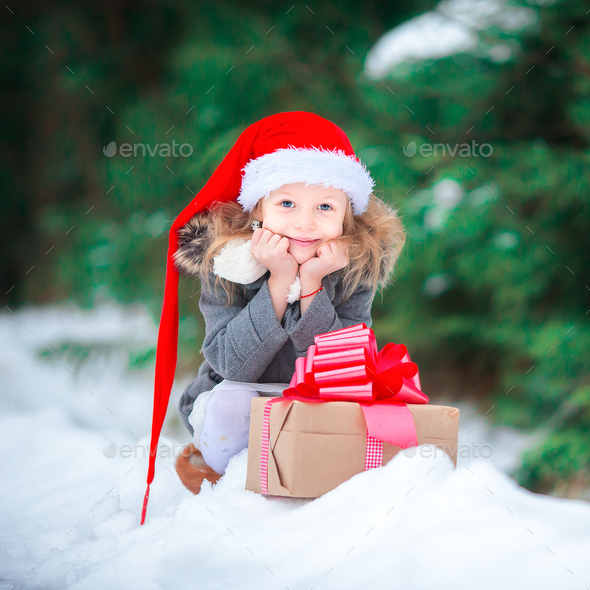 Adorable happy girl with christmas box gift in winter outdoors on Xmas eve - Stock Photo - Images