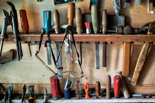 Several chisels, hammer, and other tools hanging in wooden wall - Stock Photo - Images