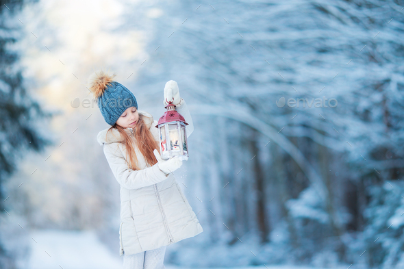 Adorable little girl with flashlight on Christmas at winter forest outdoors - Stock Photo - Images