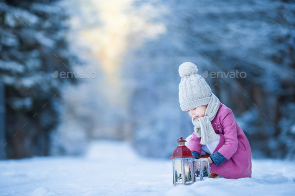 Adorable little girl with flashlight in frozen winter on Christmas outdoors - Stock Photo - Images