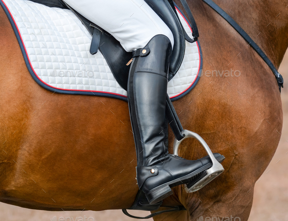 Jockey riding boot in the stirrup. - Stock Photo - Images