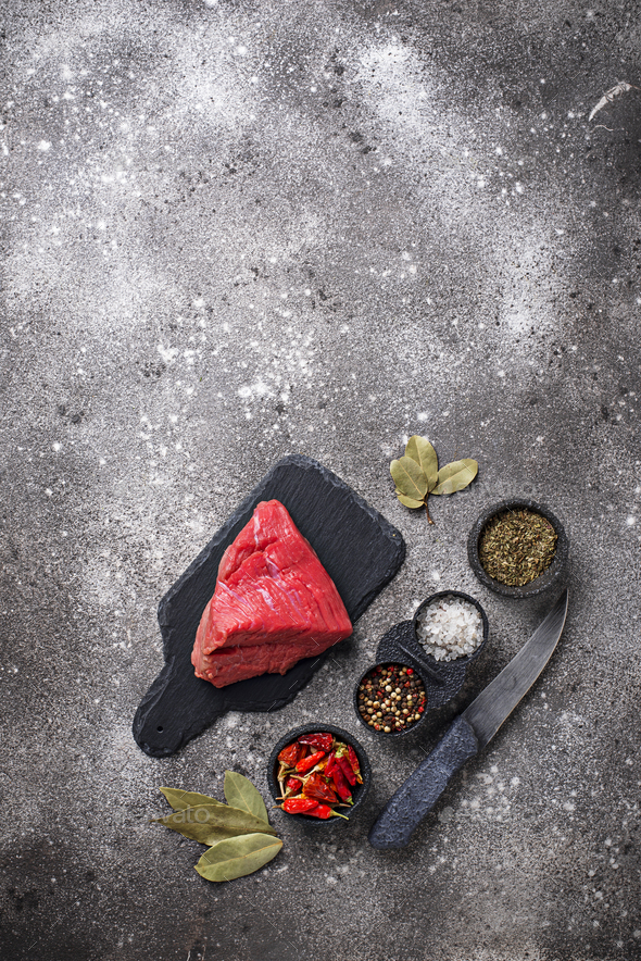 Raw meat on cutting board with spices - Stock Photo - Images