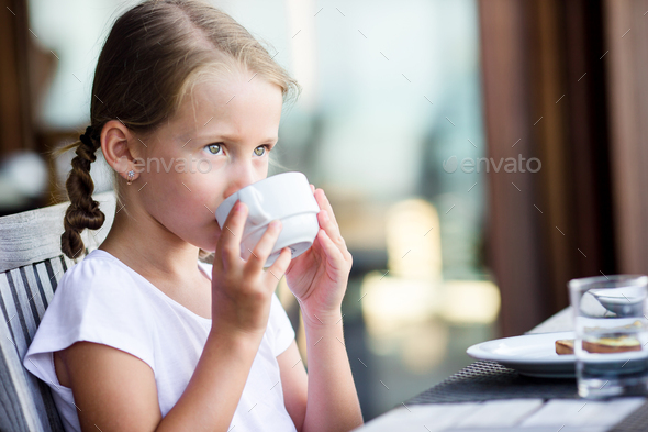 Little girl drinking cacao at outdoor cafe - Stock Photo - Images