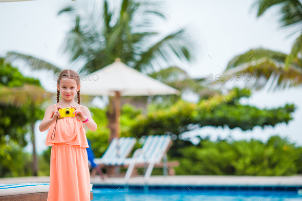 Adorable little girl making selfie near a swimming pool - Stock Photo - Images