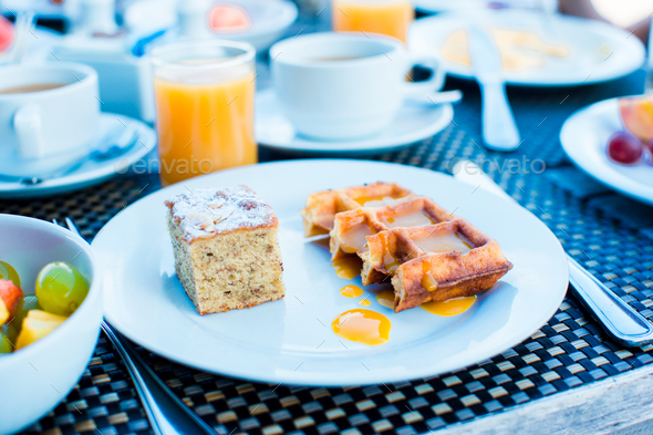 Fresh fruit salad, waffles, cake, coffee and juice served for breakfast at resort restaurant - Stock Photo - Images