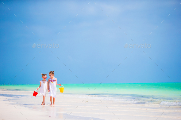 Adorable little girls having fun on the beach together - Stock Photo - Images