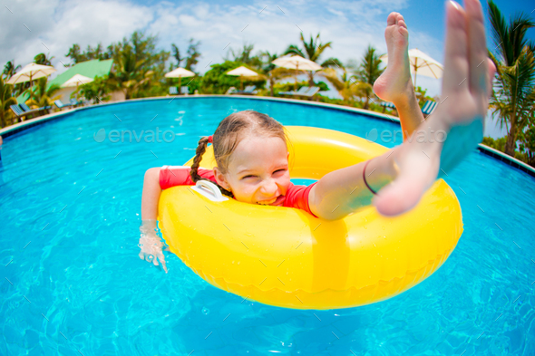 Portrait of happy child with inflatable rubber circle having fun in swimming pool - Stock Photo - Images