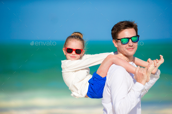 Little girl and father at tropical beach having fun - Stock Photo - Images
