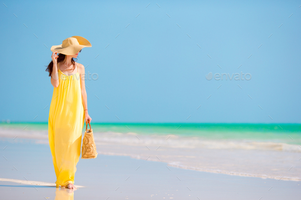 Young beautiful woman in big hat during tropical beach vacation - Stock Photo - Images