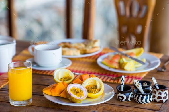 Tasty exotic fruits - ripe passion fruit, mango on breakfast at outdoor restaraunt - Stock Photo - Images