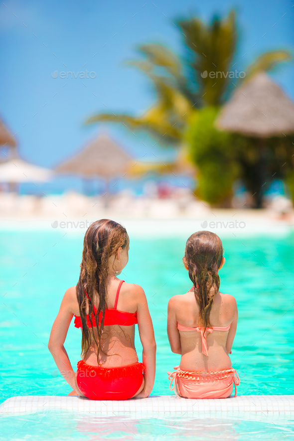 Adorable little girls playing in outdoor swimming pool - Stock Photo - Images