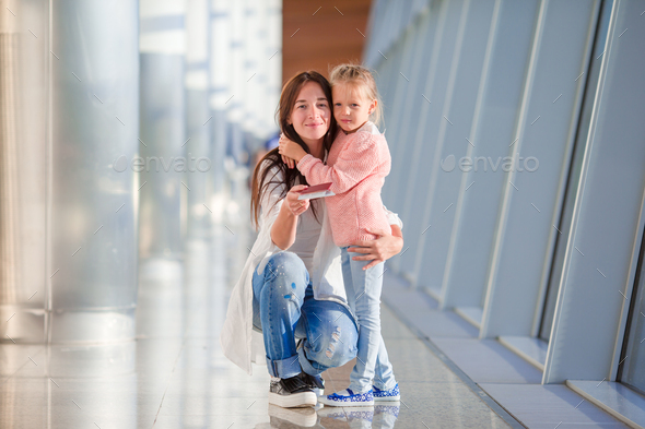 Mother and little girl in airport waiting for boarding - Stock Photo - Images