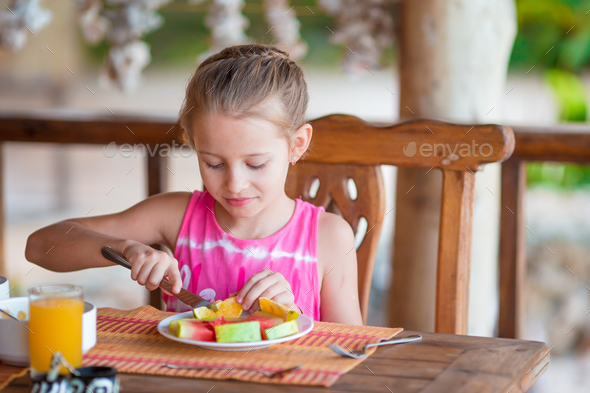 Adorable little girl having breakfast at outdoor cafe - Stock Photo - Images