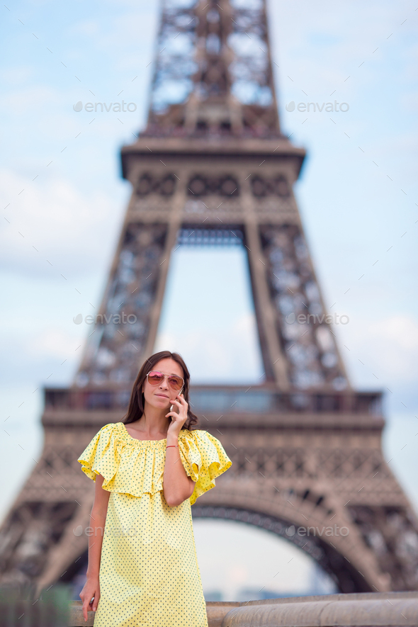 Young woman talking by phone background Eiffel Tower in Paris - Stock Photo - Images
