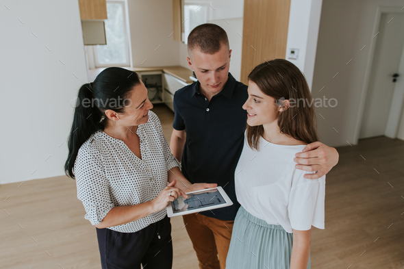 Estate agent with digital tablet showing young couple new apartment. - Stock Photo - Images