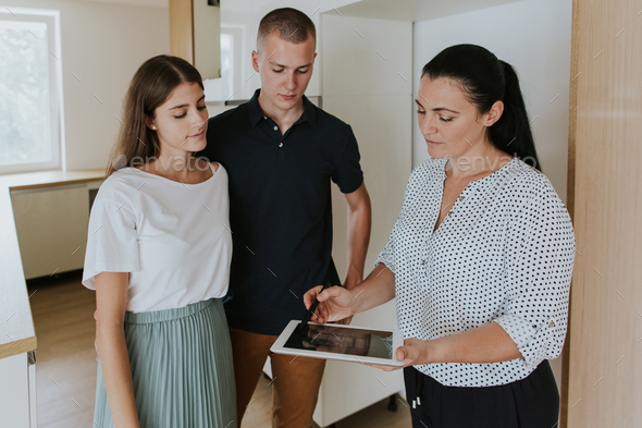 Estate agent showing young couple digital tablet in new house. - Stock Photo - Images