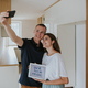 Young couple with digital tablet taking selfie in new house. - PhotoDune Item for Sale