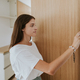 Portrait of young woman adjusting thermostat in new apartment. - PhotoDune Item for Sale