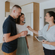Estate agent handing keys to young couple in new house. - PhotoDune Item for Sale