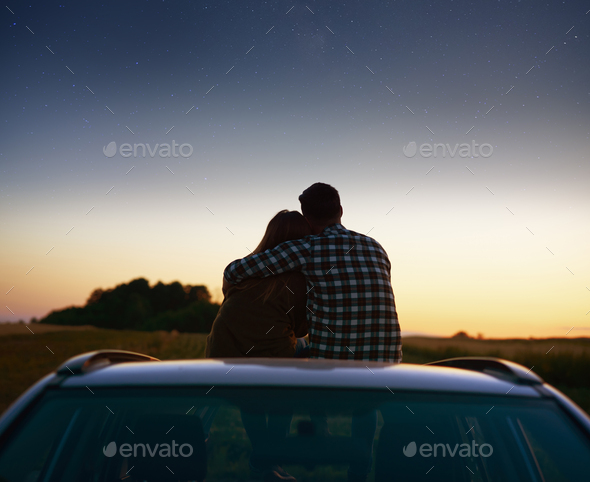 Rear view of loving couple enjoying the view at night - Stock Photo - Images