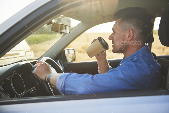 Young man driving a car and drinking coffee in a rush - Stock Photo - Images