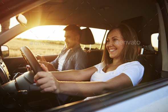 Smiling woman driving a car - Stock Photo - Images