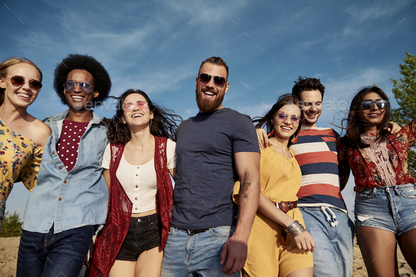 Young smiling people in a row on the fresh air - Stock Photo - Images
