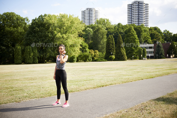 Young woman catching a short break during jogging - Stock Photo - Images