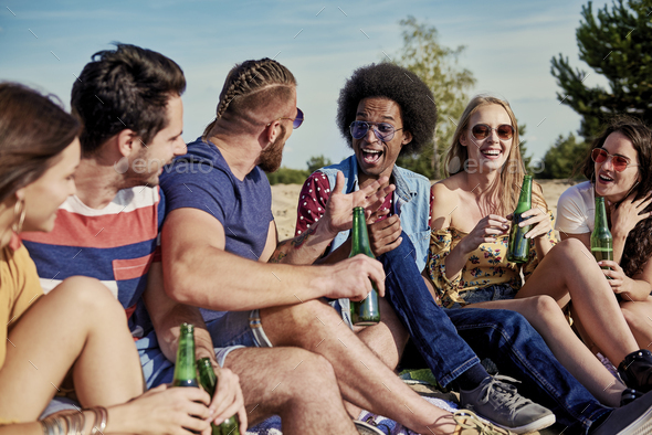 Six young people drinking beer outside - Stock Photo - Images