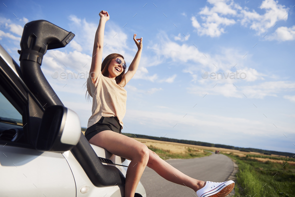 Woman with hands raised sitting on car - Stock Photo - Images