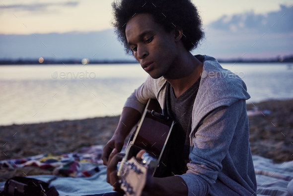 African man playing the guitar on the beach at night - Stock Photo - Images