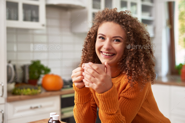 Smiling young woman drinking hot tea in the kitchen - Stock Photo - Images