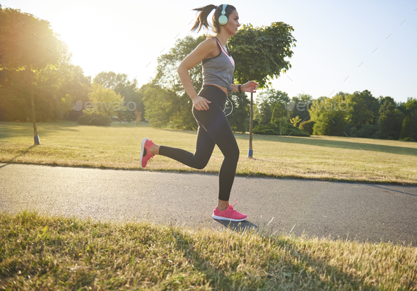 Side view of young woman running and listening to music - Stock Photo - Images
