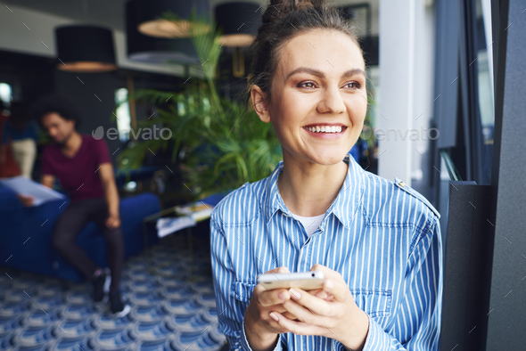 Office worker using the cell phone over work - Stock Photo - Images