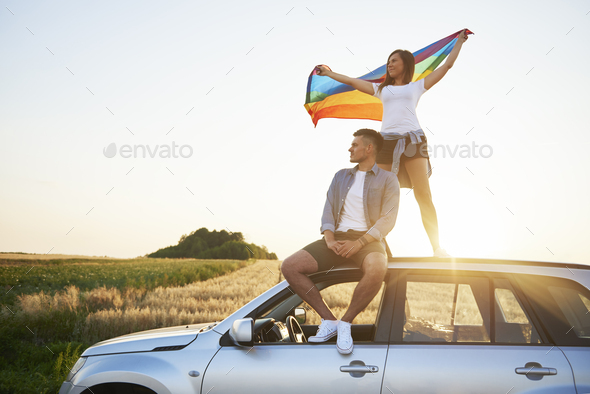 Young couple with rainbow flag enjoying the view - Stock Photo - Images