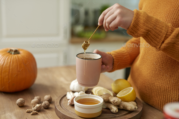 Woman making hot tea with honey - Stock Photo - Images