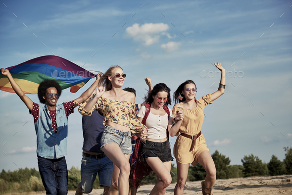 Happy friends with rainbow flag running outdoors - Stock Photo - Images