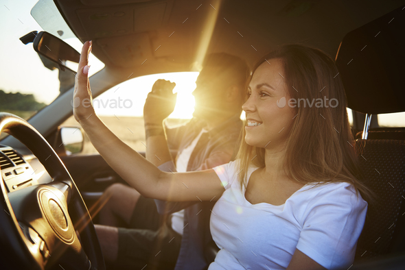 Playful couple dancing and singing during road trip - Stock Photo - Images