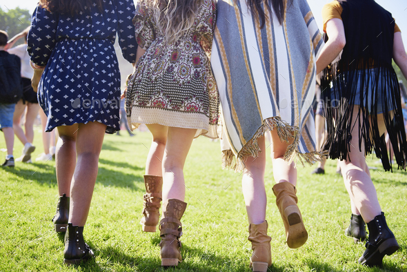 Rear view of four women running at the music festival - Stock Photo - Images